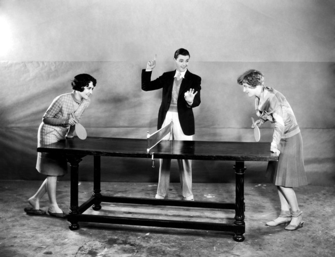 circa 1925: Hollywood film star, Dorothy Sebastian (1903 - 1957) (right) about to start a game of table tennis with fellow actress, Joan Crawford (1904 - 1977). The umpire is actor, Eddie Nugent (1904 - 1995). (Photo by Margaret Chute)